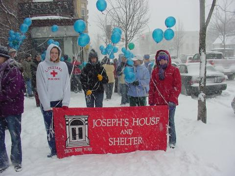 Walkers in the snow carrying a Joseph's House banner.