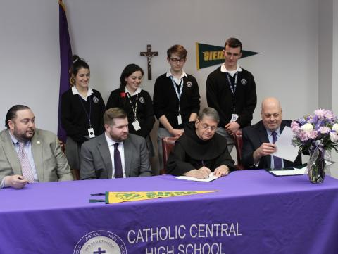 "Catholic Central High School students look on as Siena College President signs the formal agreement of the ""Crusader to Saint"" Academic Partnership Program. Seated left to right are Giovanni Virgiglio, Superintendent of Schools; Ridge Harris, Chairman of the Board of Trustees of CCHS; Br. Ed Coughlin, President of Siena College; Christopher Signor, Principal of Catholic Central"
